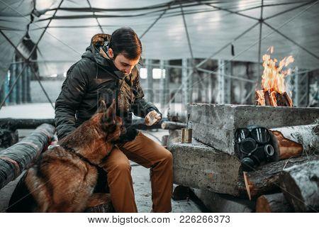 Stalker feeding a dog, apocalypse concept