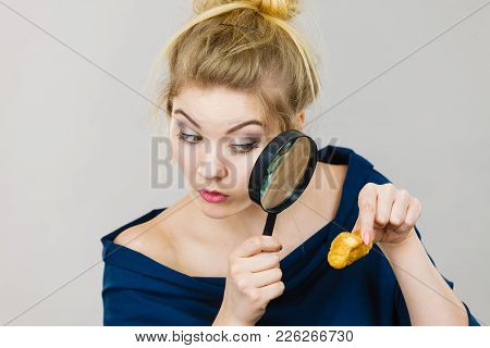 Blonde Woman Holding Magnifying Glass Investigating Piece Of Bread. Gluten Products, Food Ingredient