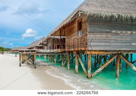 Beautiful Tropical Sunset Landscape With Wooden Villas Over Water Of The Indian Ocean, Maldives Isla
