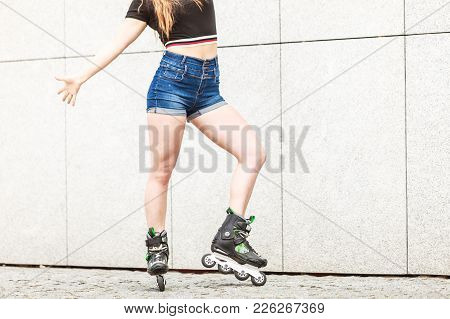 Woman Legs Wearing Roller Skates Riding In Town. Female Being Sporty Having Fun During Summer Time.