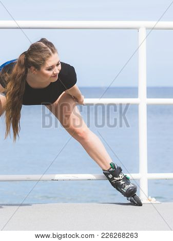 Attractive Young Woman Wearing Roller Skates Relaxing After Ride. Fit Female Having Fun During Summe