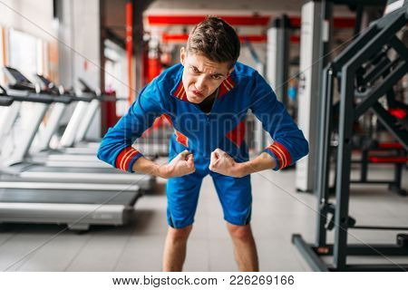 Skinny man in sportswear shows his muscles, gym