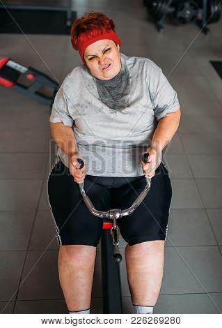 Fat sweaty woman, training on exercise machine