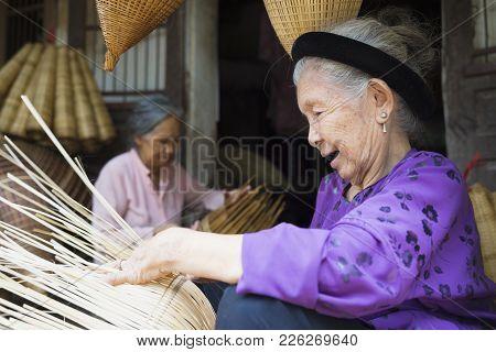 Hung Yen, Vietnam - July 26, 2015: Old Woman Weaves Bamboo Fish Trap At Vietnamese Traditional Craft