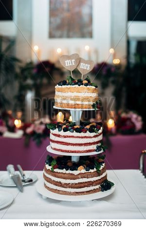 Three-tiered Wedding Cake With Blueberries, Raspberries And Berries, Two Heart Form Plates On The To