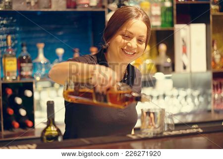 A Bartender Woman Pours A Glass Of Whiskey To A Client In The Hotel Bar. Shelves With Bottles Of Alc