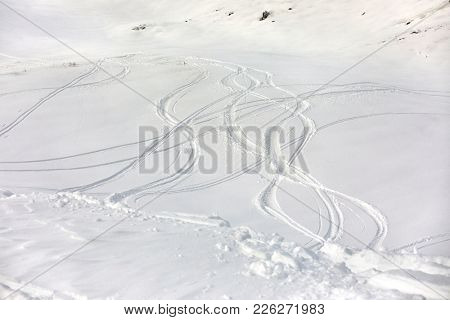 Skier' and snowboarder's curves in the snow