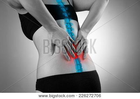 Pain In The Spine, Woman With Backache, Injury In The Lower Back, Black And White Photo With Highlig