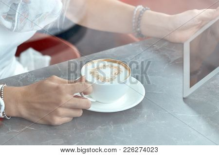 Woman Looking At Touch Pad Screen While Standing In Cafe
