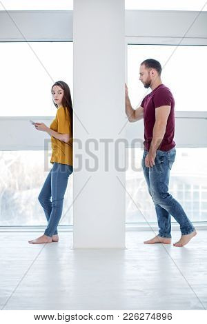 Hard Feelings. Pretty Upset Young Woman Holding Her Phone And Standing Near The Wall And Her Boyfrie
