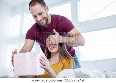 Gift For You. Good-looking Exuberant Muscular Man Closing His Girlfriends Eyes And Making A Surprise