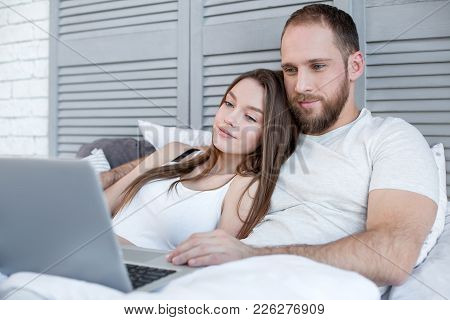 Watching A Film. Beautiful Loving Happy Couple Relaxing And Lying In Bed And Watching A Film Togethe
