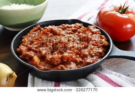Bolognese Sauce With Parmesan Cheese In A Cooking Pan Or Iron Pan. Italian Cuisine Background With P