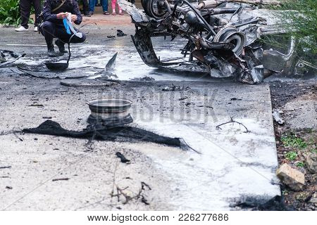 Crowd In Background. Burned Car After An Accident On The Road. Police At The Scene Of The Accident.