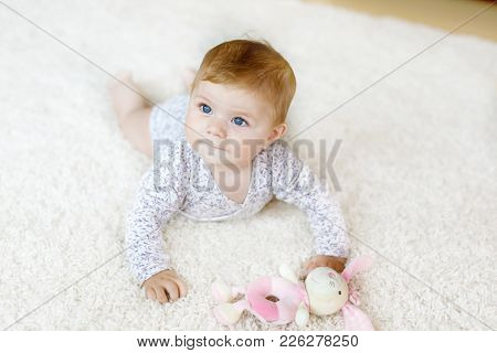 Little Funny Baby Girl Lifting Body And Learning To Crawl.