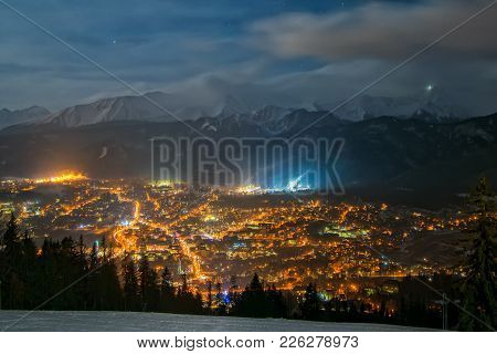 Scenic nightscape of Zakopane, Poland. Majestic aerial view from Gobalowka mountains with citylights above and Tatra snowcaped peaks in background