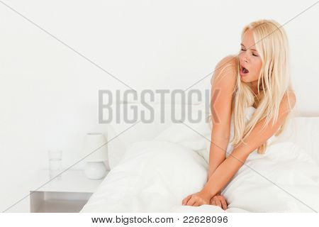 Blonde woman yawning sitting on her bed