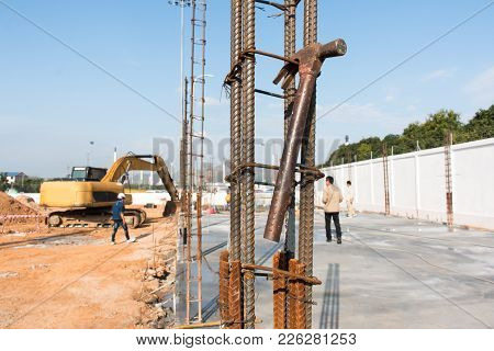 Hammer Hanging Steel Wire Tie With Construction Worker At Outdoor.