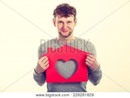 People, Fresh Start, Real Estate And Love Concept. Young Enjoyable Enamoured Man Holding Red House W