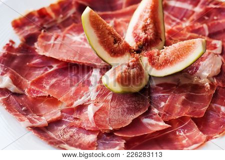 Spanish Cuisine Tapas Food Jamon With Fig. Beautiful Appetite Slices Of Raw Pork Meat, White Plate B