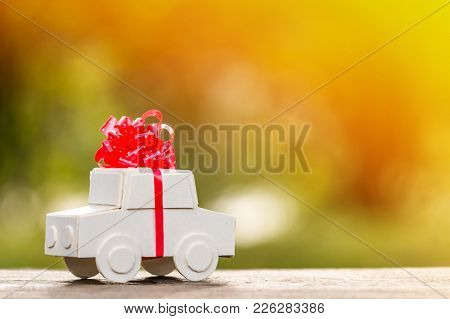 Car Model Tied With Red Ribbon Put On The Wood In Public Park , Loan And Saving For Buy A New Car As