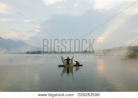 Hanoi, Vietnam - June 5, 2016: Lake Scene At Twilight With A Couple Of Fishers Catching Fish By Net
