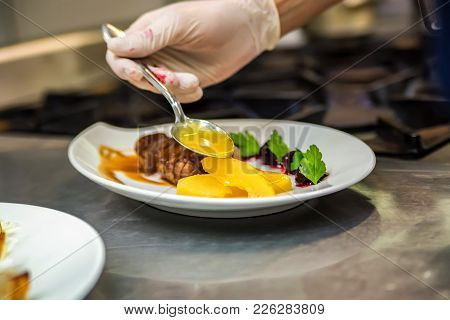Hand Adds Sauce To Steak