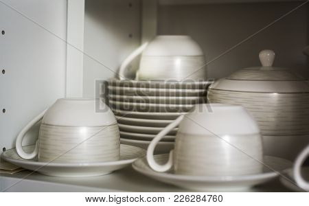 Decorated Coffee Cups And Saucers On The Shelf Of A White Pantry