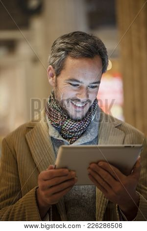 A Handsome Man Using A Digital Tablet Outside With City Lights At The Background