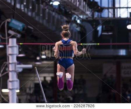 A Female Pole Vaulter Falling In The Air After Clearing A Height In A Pole Vault Competition, From B