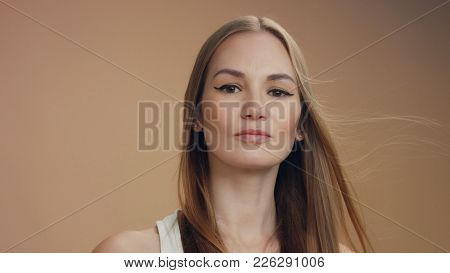Woman's Portrait Joying Of Wind Moving Her Straight Hair Slowly