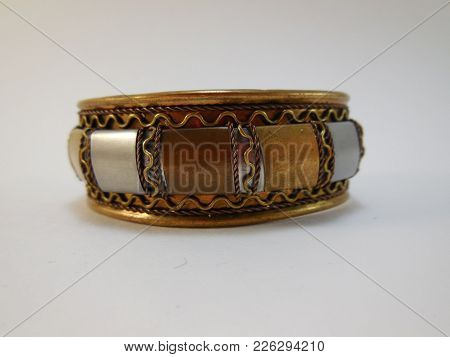 Indian Bracelet Made Of Brass With Multi-colored Metal Insets Lying On White Background