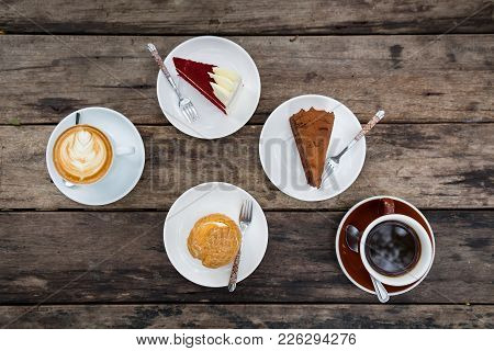 Close-up Of Shu Cream (japanese Cream Puff), Red Velvet Cake, Chocolate Cake, And Hot Coffee On Wood