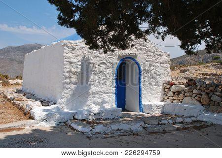 A sign saying Agios Ioannis (translation- Saint John) on the entrance to the church of Agios Ioannis at Livadia on the Greek island of Tilos.