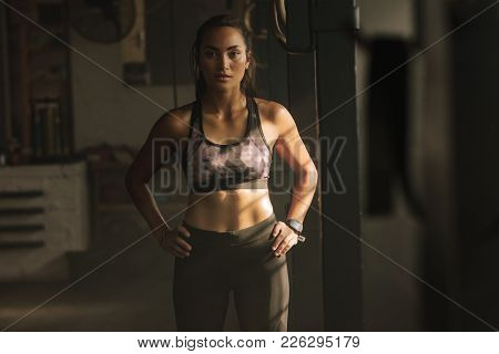Young Fitness Woman Standing With Hands On Hips In The Gym. Strong Woman In Sportswear Standing In H
