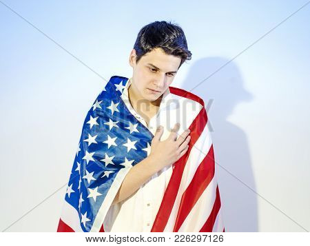 A Young Handsome Man Wrapped In A National Flag - The United States, Laid His Hand On His Heart. Oat