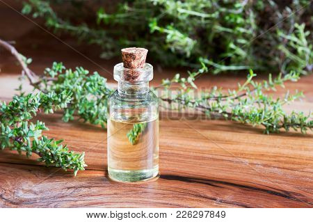 A Bottle Of Thyme Essential Oil With Fresh Thyme Twigs In The Background