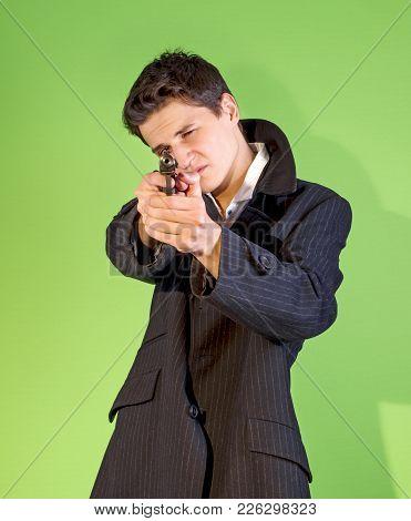 Handsome Young Man Aiming A Gun At The Camera.
