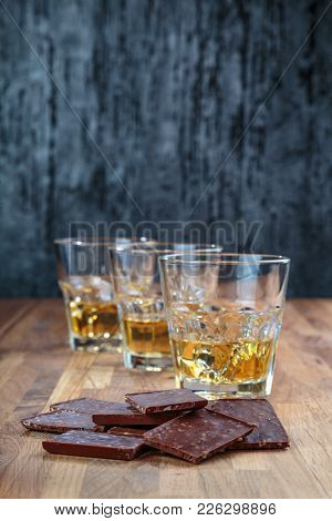 chocolate and three glasses of whiskey on the oak surface of the table