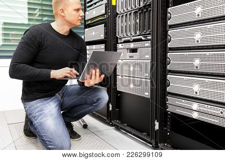 Mid Adult It Consultant With Laptop Monitoring Servers In Datacenter