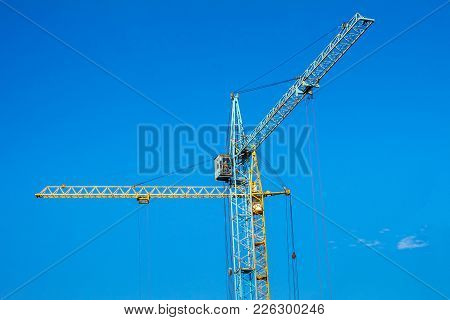 Two Cranes Against The Blue Sky.