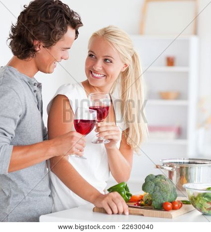 Portrait of a couple having a glass of red wine while cooking