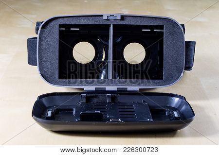 Virtual Reality Goggles On A Wooden Table. Goggles And Computer Accessories.