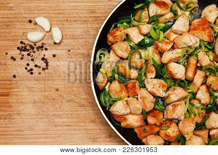 Roasted Chicken With Leek In A Frying Pan On Wooden Background. Grilled Chicken. Homemade Food. Flat