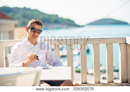 Young Successful Business Man Enjoying Espresso Coffee Beverage In Sunny Marine Panoramic Cafe.hands