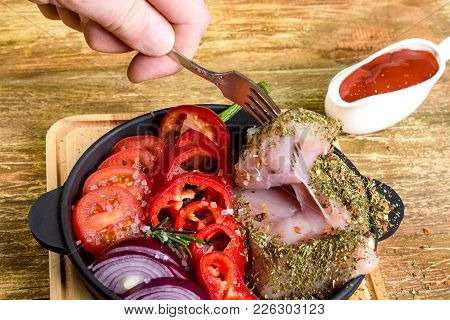 Hands Chef Bring Up With Fork Prepared For Cooking Raw Chicken Fillet, In A Frying Pan With Tomatoes