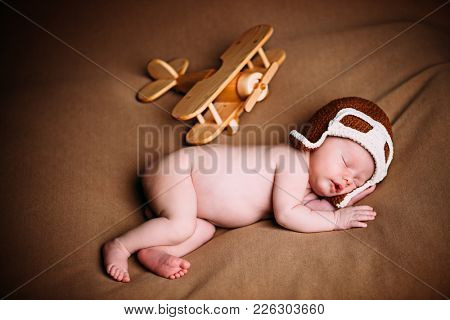 Portrait of a cute newborn baby in pilot's hat is sleeping near the toy airplane.