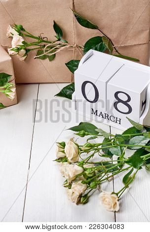Save The Date March 8 On Wooden Cube Calendar, Gift Boxes Wrapped In Craft And Fresh Pastel Roses On