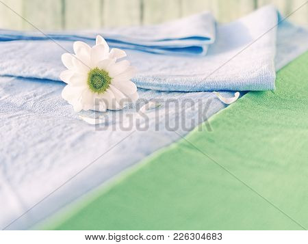 The Flower Of The White Chrysanthemum Is Covered With A Blue Linen Cloth. Nearby Is A Diagonally Loc