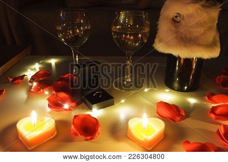 Close Up View Of A Romantic Dinner Table With Glasses Of Wine, Roses, Candles And A Engagement Ring
